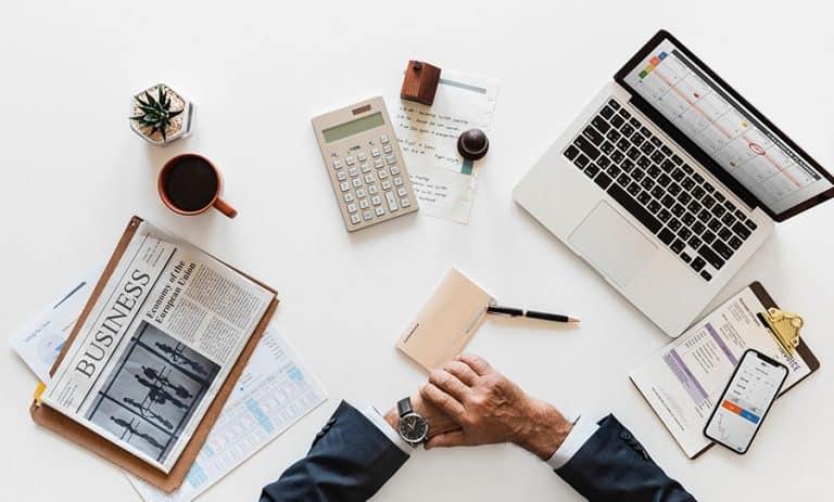 Tischfäche mit Hände, Laptop, Zeitung, Taschenrechner, Kaffee, Pflanze
